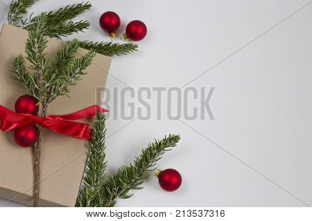 A Christmas gift box with a red bow with rosemary greens and ornaments. Frame left justified.