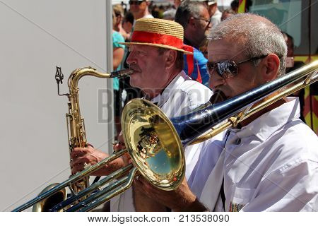 Sete, Herault, France  - Aug 21 2017: Saxaphone And Trombone Players In The Traditional French Band