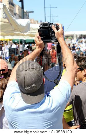 Sete, Herault, France  - Aug 21 2017: Man With A Pentax Dslr Taking Photographs Over The Heads Of To