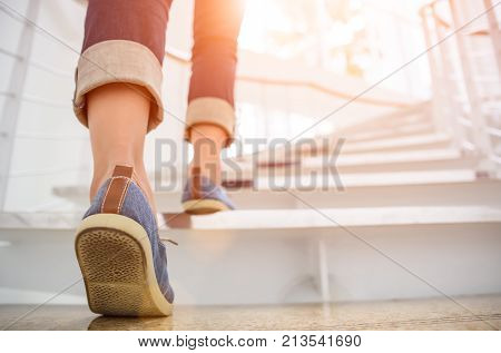 Young adult woman walking up the stairs with sun sport background.
