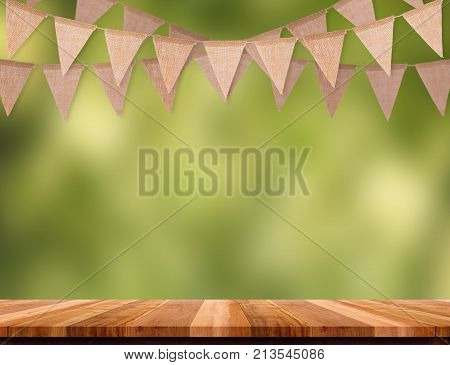 Craft brown flag banner hang over wood table with blur green tree bokeh background Template mock up for montage of product.party garland holiday backdrop for display design.wedding background