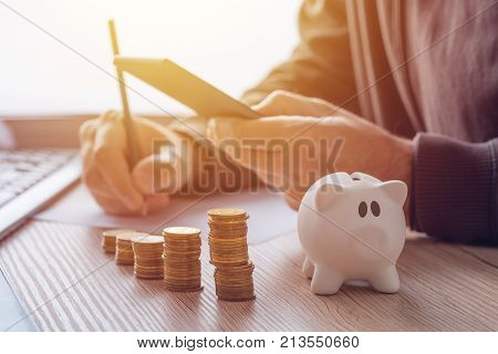Savings finances economy and home budget calculations. Close up of man doing calculations and writing notes at home.
