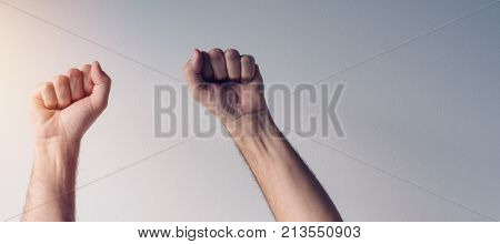 Clenched fists and arms raised in victorious manner male hands up in the air as symbol of victory and success
