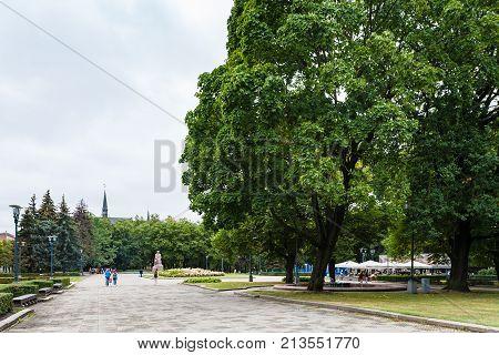 People Walk In Urban Esplanade Park In Riga