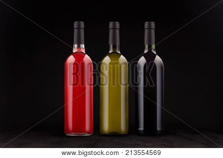 Wine bottles set - red green rose - mock up on elegant dark black wooden background. Template for portfolio advertising design branding identity cover magazine bar and restaurant menu.
