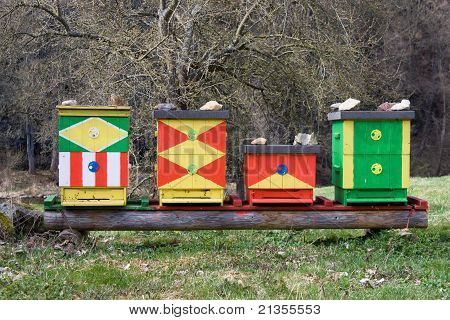 Four Colored Beehives In The Nature