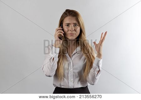 Long-haired Businesswoman In Formal Clothes Talking On The Phone With An Indignant Dismayed Displeas