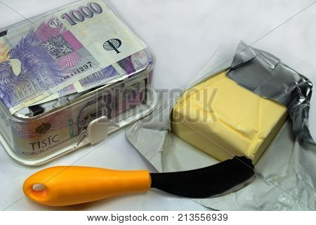 The expensive butter and yellow knife and Czech crowns / The butter box /churn/ full of Czech banknotes and unpacked butter.