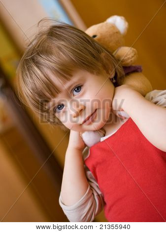 Portrait Of Cute Little Girl With A Teddy-bear Behind Her Neck