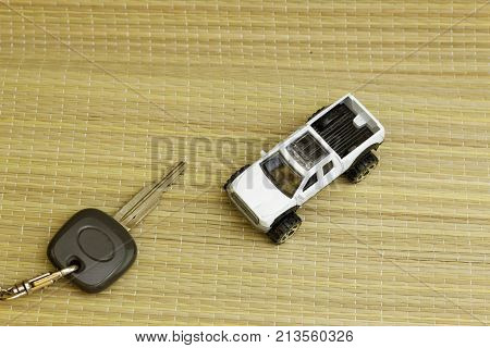 A car key and mini white pick up truck. Concept.