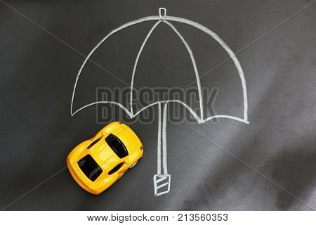 Miniature yellow car on blackboard under an umbrella drawn on the blackboard. Light mimicking sunlight come from one side of the board. Concept of protection. Conceptual.