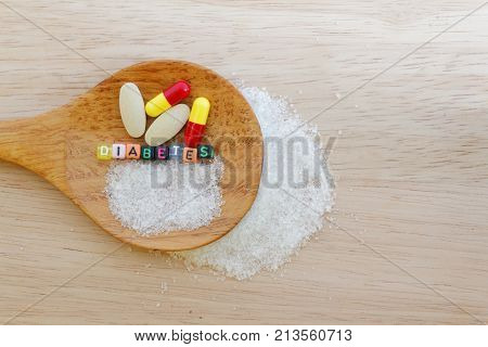 Medicine and the word Diabetes and sugar in spatula on wooden background