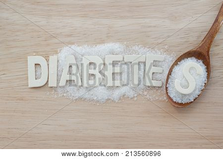 Diabetes concept. Alphabet with word DIABETES with sugar and wooden spoon on wooden background. Aphabet S on heap of sugar in wooden spoon.