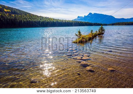 Charming little island near the shore. The gulf of lake Minnewanka. The pure water of the lake reflects coniferous forests. The concept of ecological and active tourism