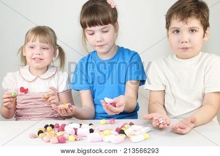 Three happy children sit with candies and marshmallows at table in white studio