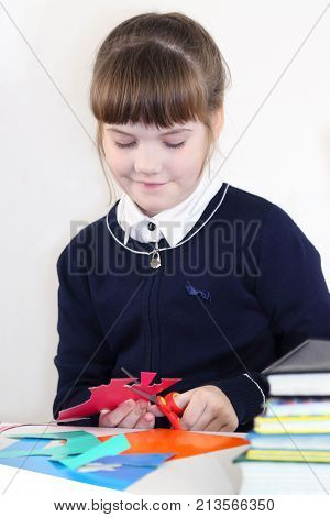 Smiling school girl cuts out with scissors from colored paper on table with books