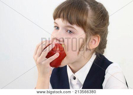 Portrait of pretty schoolgirl in uniform eating red apple in white studio