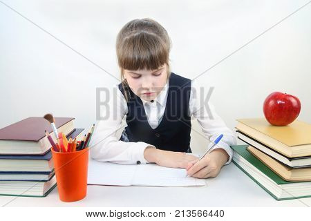 Schoolgirl sits at table and writes among books and apple in white studio