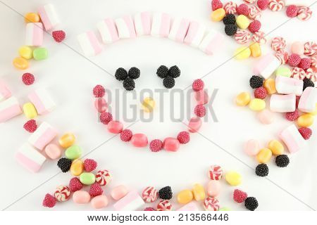 Many sweet candies and marshmallows in face shape on white surface top view