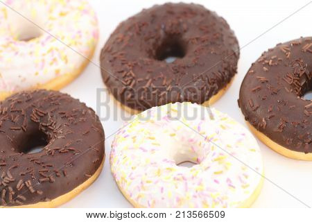 Five appetizing sweet white and chocolate donuts above view