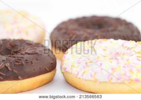 Four appetizing sweet white and chocolate donuts close up view