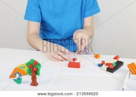 Girl hands molding house tree flowers from plasticine on table in white room