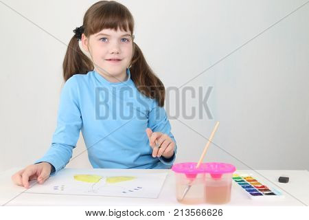 Smiling girl watercolor paints butterfly on table in white room