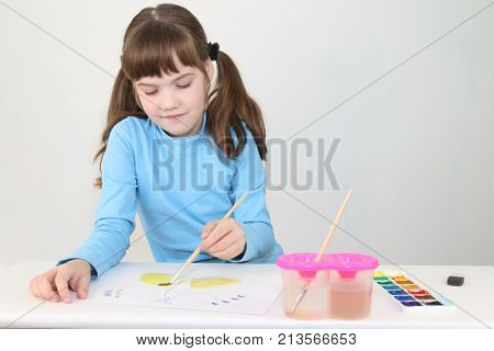 Smiling girl in blue watercolor paints butterfly on table in white room