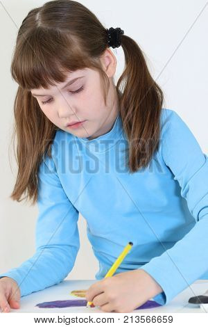 Happy girl paints watercolor butterfly with pencil on table in white room