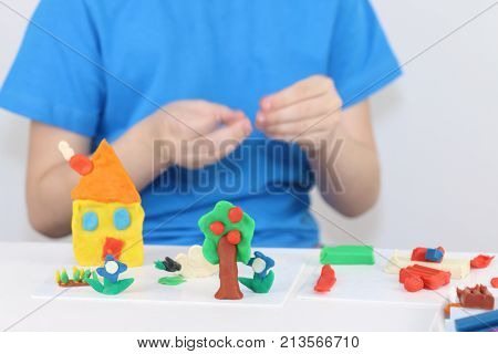 Child hands molding bright house sheep flowers from plasticine on table in room