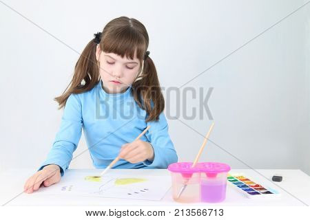 Pretty girl in blue watercolor paints butterfly on table in white room
