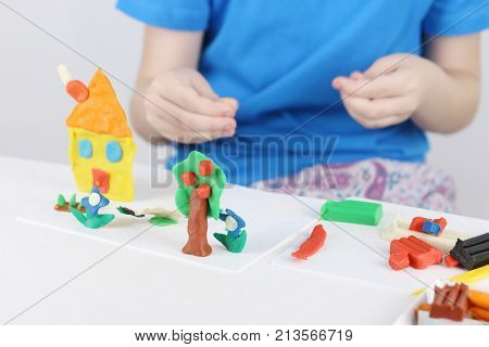 Child hands molding bright house tree flowers from plasticine on table in room