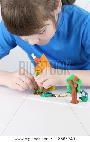Girl molds house tree flowers from plasticine on white table in white room