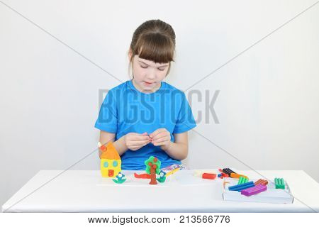 Pretty girl in blue molds house from plasticine on white table in white room