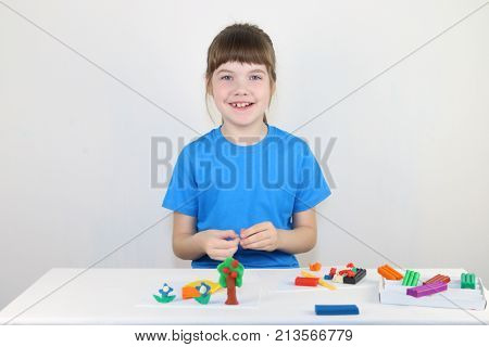 Happy girl in blue molds from plasticine on white table in white room