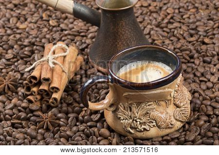 Strong fragrant cooked coffee with foam. A coffee drink in a cup. A cup of coffee on coffee beans. Freshly brewed coffee in a pot. Cinnamon near the cup with coffee and cezve on the grains