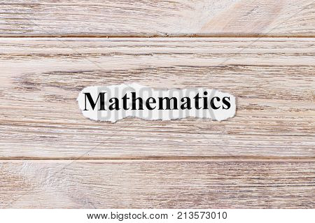 Mathematics of the word on paper. concept. Words of Mathematics on a wooden background.