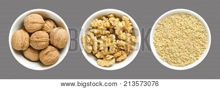 Whole, walnuts, kernel halves and ground walnuts in white bowls on gray background. Seeds of the common walnut tree Juglans regia, used as snack or for baking.  Macro food photo close up from above.
