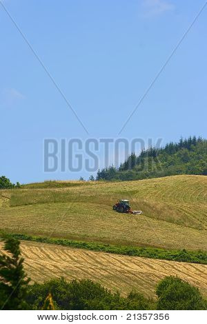 Tractor In A Field Over A Hill