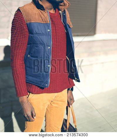 Fashion Man In A Red Knitted Sweater, Vest Jacket Stands In The City