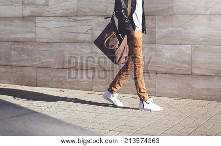 Fashion Man Wearing Black Leather Jacket With Bag Walking At Evening City Background