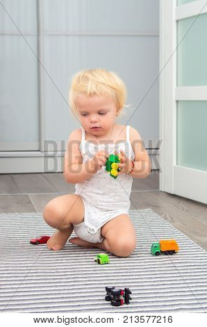 Blond Baby Girl Playing Toy Cars At Home