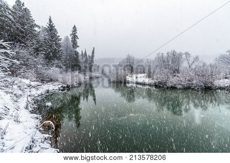 A cooling river with the first snow on the shore on a cold day of late autumn