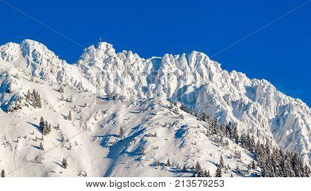 High mountain with summit cross under deep snow on sunny winter day. Rauhhorn, Allgau, Bavaria in Germany.
