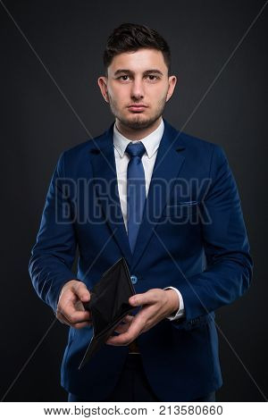 Broke Businessman With Empty Wallet On Dark Background.