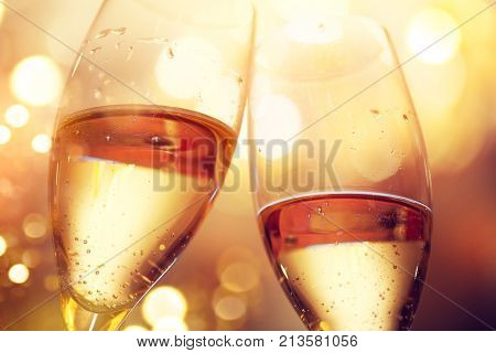 Christmas and New Year celebration with champagne. New Year holiday glowing gold background. Two Champagne Glasses