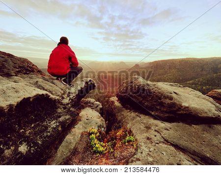 Hiker man take a rest on mountain peak. Man lay on summit bellow autumn valley. Bright morning Sun shining in sky.