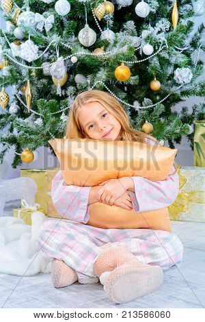 Happy eight year old girl in pajama sitting under the Christmas tree with her pillow. Christmas concept. Gifts and miracles.