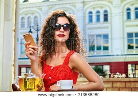 Charming brunette woman with beautiful smile using her smartphone while resting and drinking tea in a summer café.