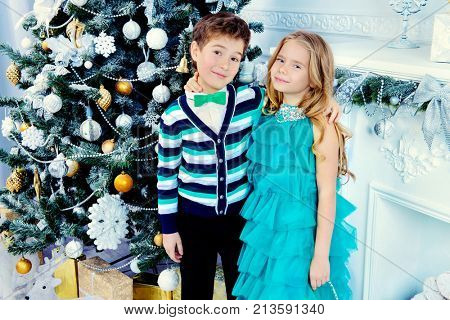 Christmas, fashion concept. Two beautiful children in elegant evening clothes posing by the Christmas tree. Classic luxurious interior decorated for Christmas.
